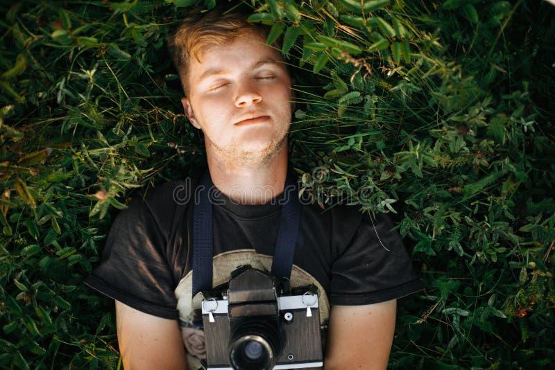 Homme élégant de hippie avec la caméra de photo de film se situant dans l'herbe verte et détendant dans le pré ensoleillé au couc photographie stock libre de droits