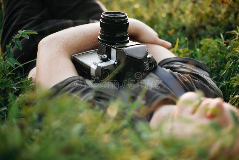 Homme élégant de hippie avec la caméra de photo de film se situant dans l'herbe verte et détendant dans le pré ensoleillé au couc photos libres de droits