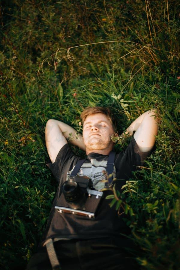 Homme élégant de hippie avec la caméra de photo de film se situant dans l'herbe verte et détendant dans le pré ensoleillé au couc photographie stock