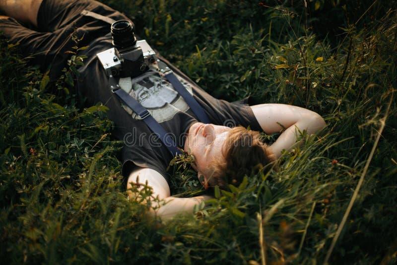 Homme élégant de hippie avec la caméra de photo de film se situant dans l'herbe verte et détendant dans le pré ensoleillé au couc image libre de droits