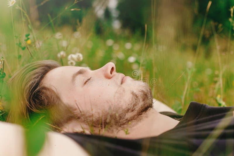 Homme élégant de hippie se trouvant sur l'herbe ensoleillée dans le pré et la détente photo stock