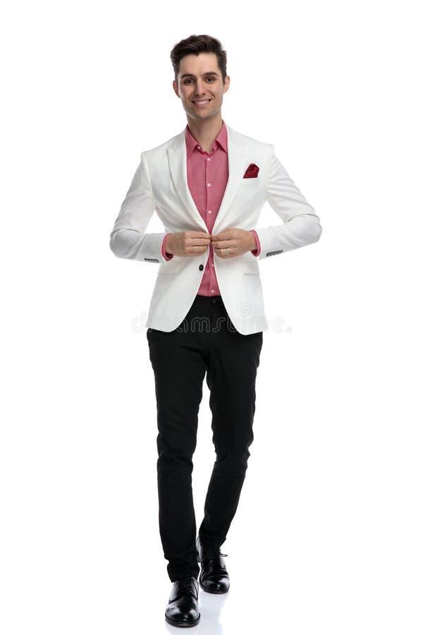 Homme élégant de sourire boutonnant son manteau et marche images libres de droits
