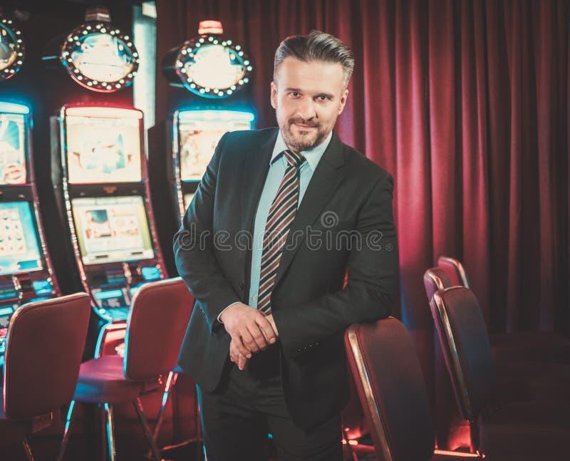 Homme élégant près des machines à sous dans un intérieur de luxe de casino images stock