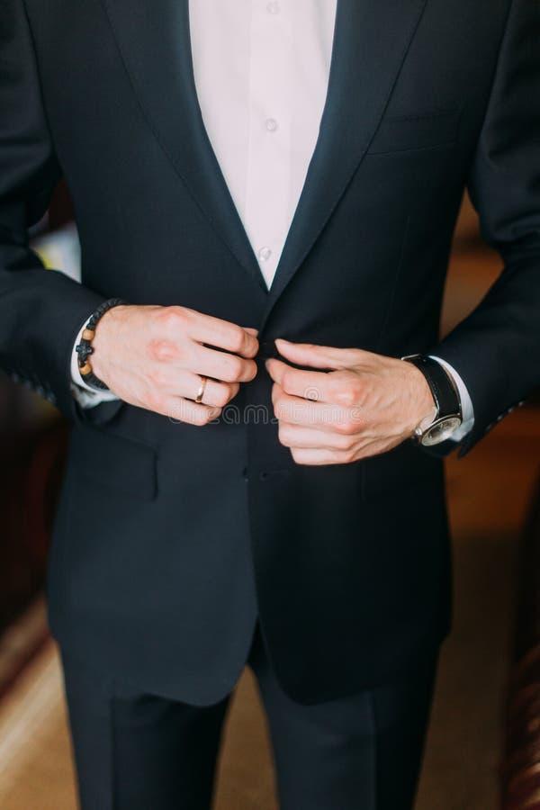 Homme élégant s'habillant dans le costume noir élégant à l'intérieur photographie stock