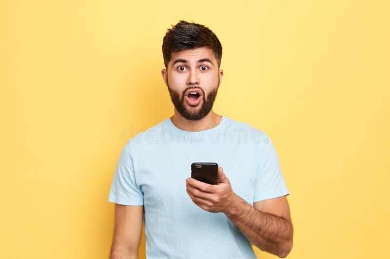 Homme émotif bel avec l'expression choquée regardant la caméra images stock