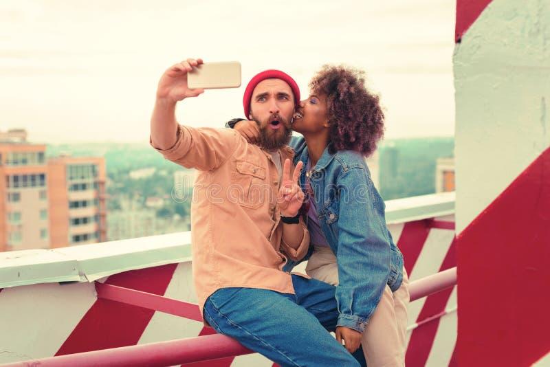 Homme émotif posant à l'appareil-photo tout en prenant des selfies avec l'amie photos stock
