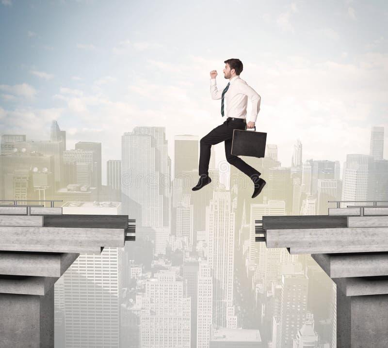 Homme énergique d'affaires sautant par-dessus un pont avec l'espace image stock