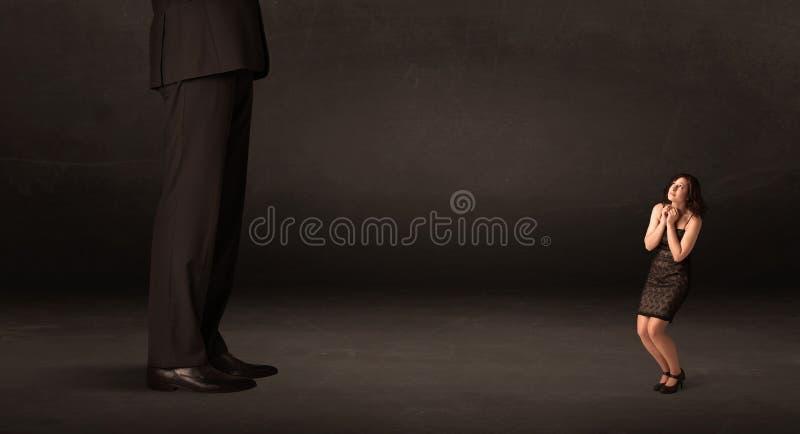 Homme énorme avec la petite femme d'affaires se tenant à l'avant le concept image libre de droits