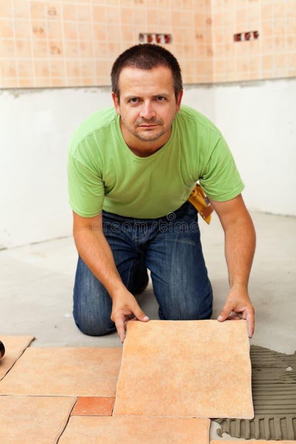 Homme étendant les carrelages en céramique image stock
