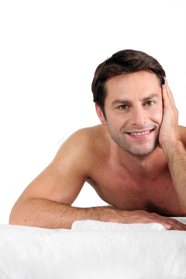 Homme étendu sur la table de massage photo stock