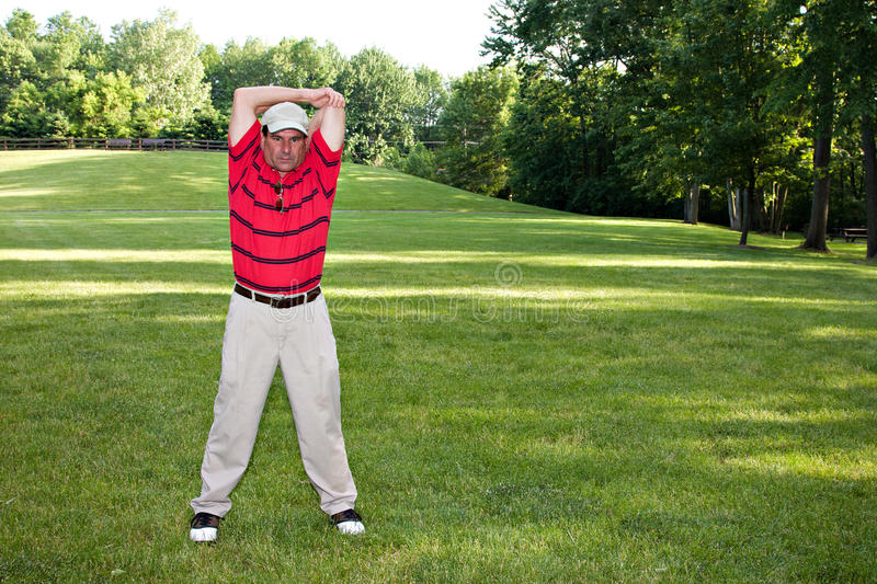 Homme étirant le golf images stock