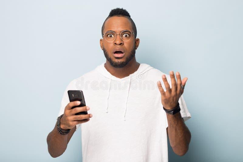 Homme ?tonn? d'afro-am?ricain recevoir le message inattendu sur le t?l?phone portable image libre de droits
