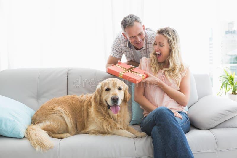 Homme étonnant son épouse avec un cadeau photographie stock libre de droits