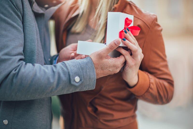 Homme étonnant son amie avec un cadeau, fin  images stock