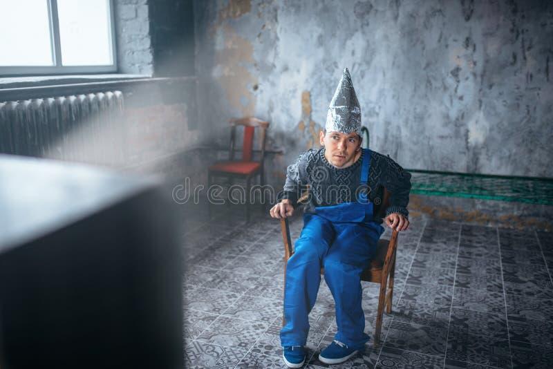Homme étrange dans la montre TV, UFO de casque de papier d'aluminium photo libre de droits