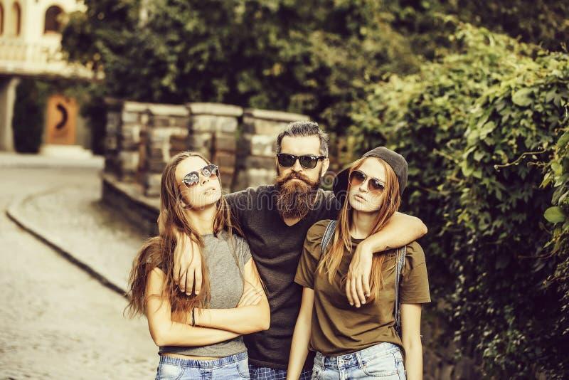 Homme étreignant deux jolies filles photos stock