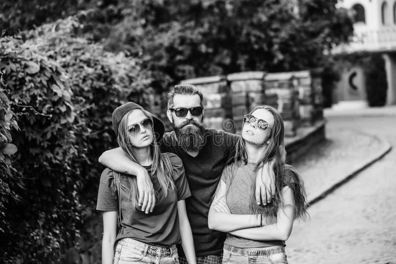 Homme étreignant deux jolies filles photo stock