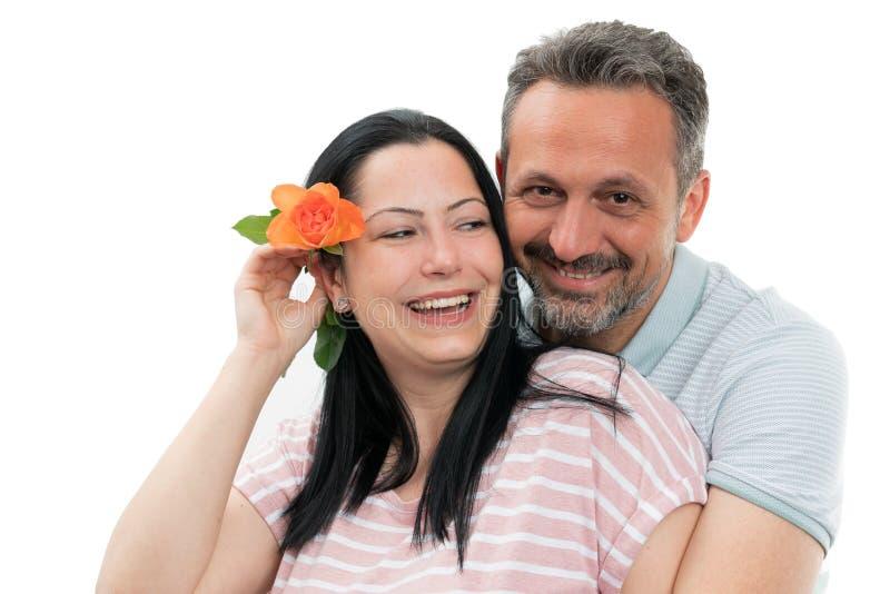 Homme étreignant la femme avec la rose derrière l'oreille images stock