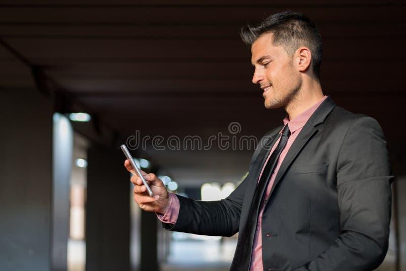 Homme étroit avec un téléphone portable photographie stock libre de droits