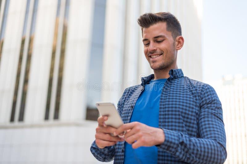 Homme étroit avec un téléphone portable photos stock