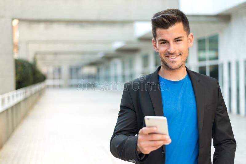 Homme étroit avec un téléphone portable photo libre de droits