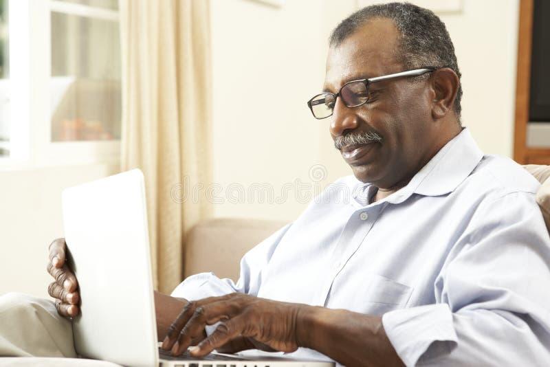 Homme aîné à l'aide de l'ordinateur portatif à la maison photo libre de droits
