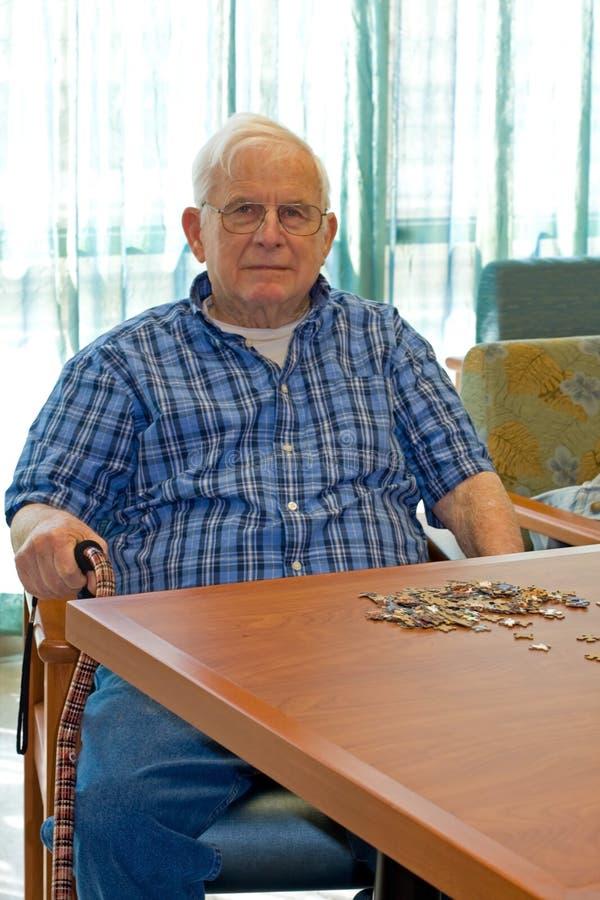 Homme aîné à la table de jeu images stock