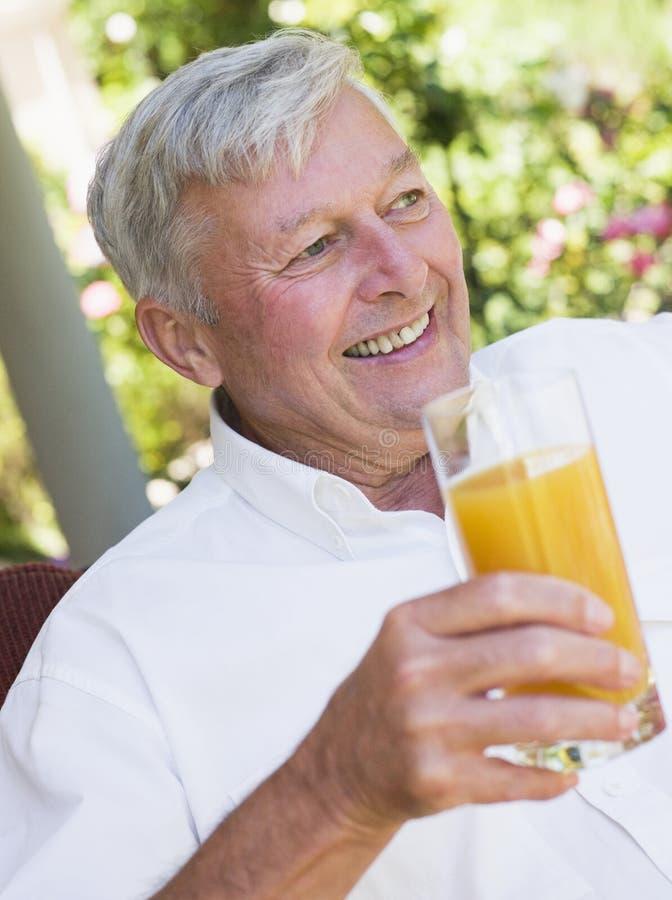 Homme aîné appréciant la glace de jus photo stock