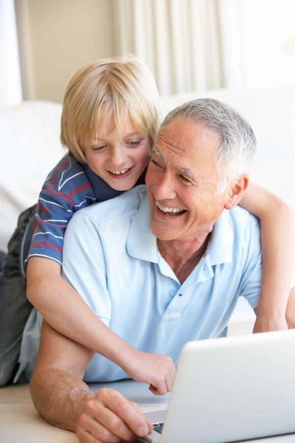 Homme aîné avec le jeune garçon à l'aide de l'ordinateur portable photographie stock libre de droits