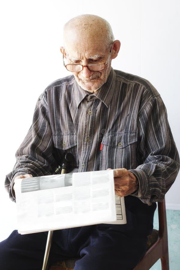 Homme aîné avec le journal photo stock