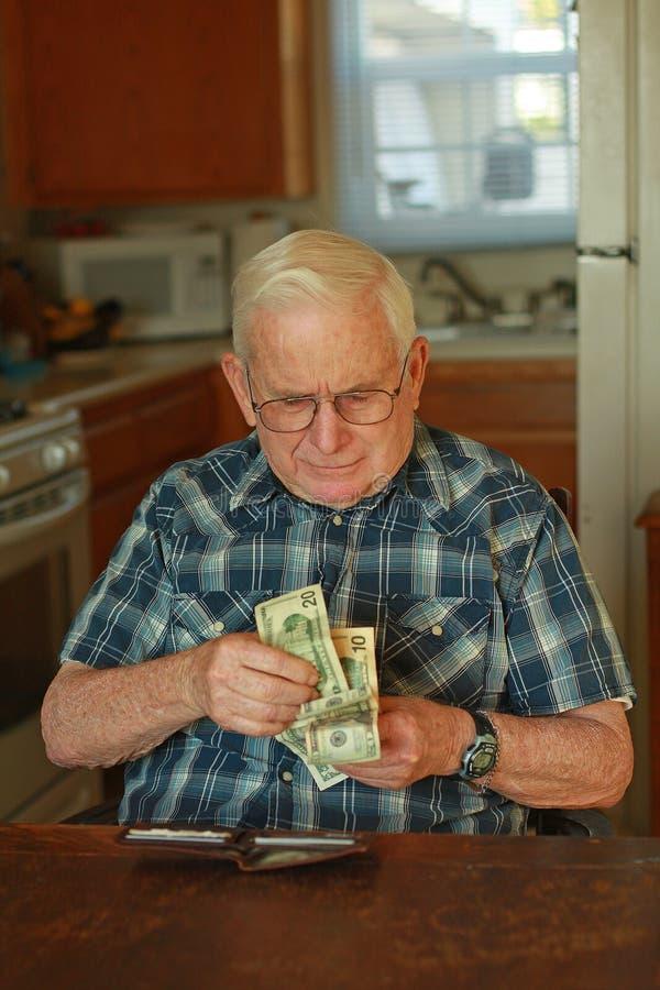 Homme aîné comptant l'argent images libres de droits