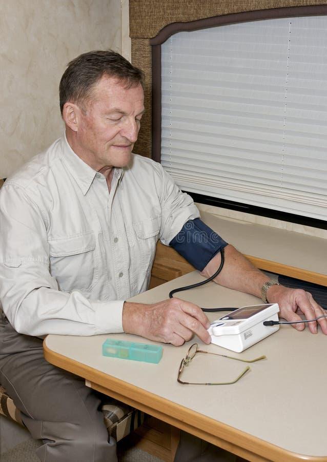 Homme aîné contrôlant la tension artérielle images stock