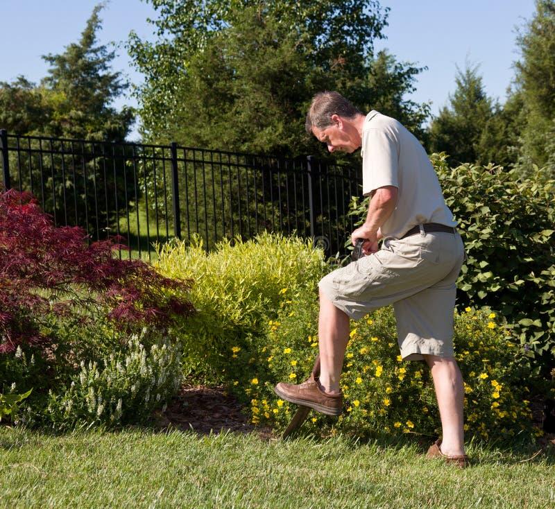 Homme aîné creusant dans le jardin photos stock
