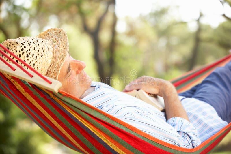Homme aîné détendant dans l'hamac photos stock
