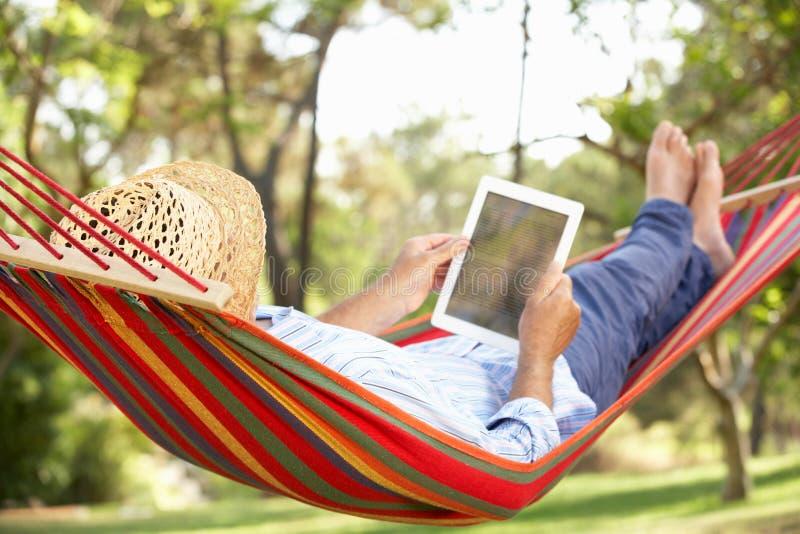 Homme aîné détendant dans l'hamac avec l'E-Livre photographie stock