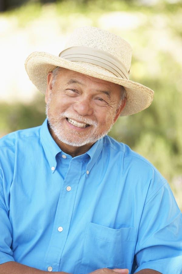 Homme aîné détendant dans le jardin photo stock