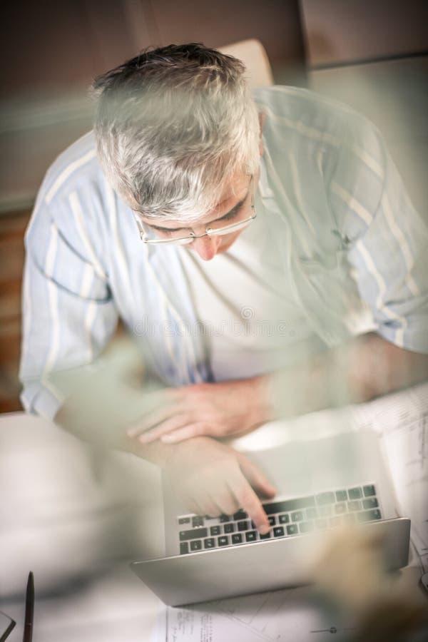 Homme aîné d'affaires travaillant sur l'ordinateur portatif image libre de droits