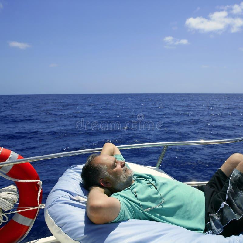 Homme aîné de marin ayant un reste sur le bateau d'été image stock