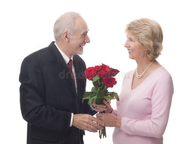 Homme aîné donnant des roses à son épouse photos stock