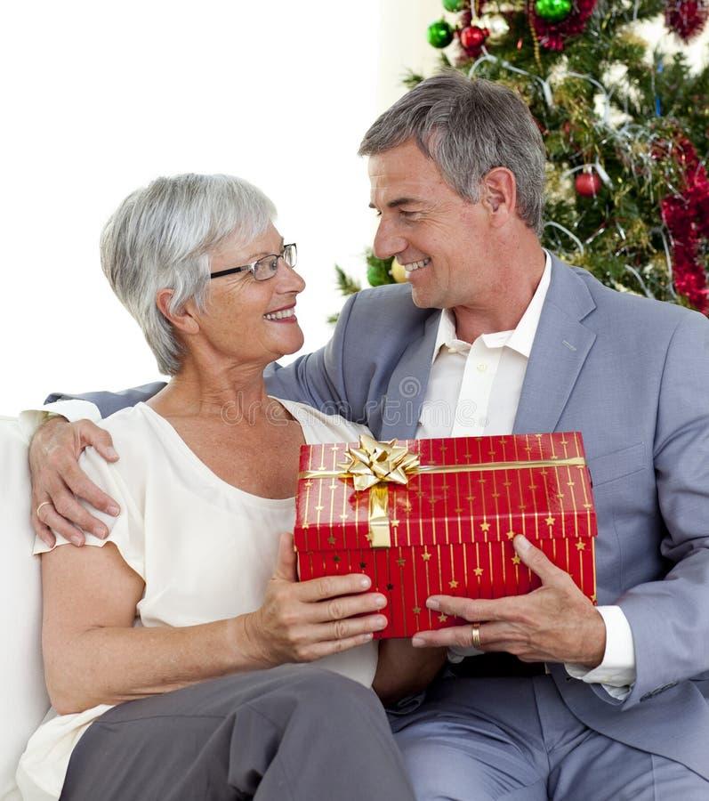 Homme aîné donnant un cadeau de Noël à son épouse images stock