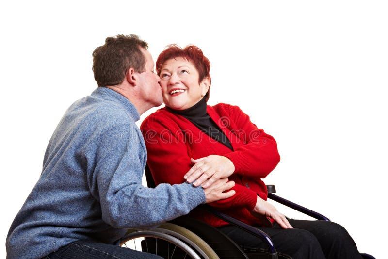 Homme aîné embrassant son handicapé photo stock
