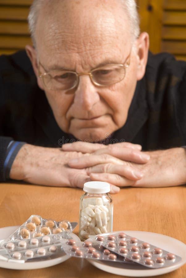 Homme aîné et ses pillules images libres de droits