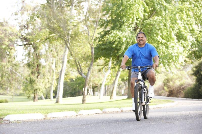 Homme aîné faisant un cycle en stationnement photos stock