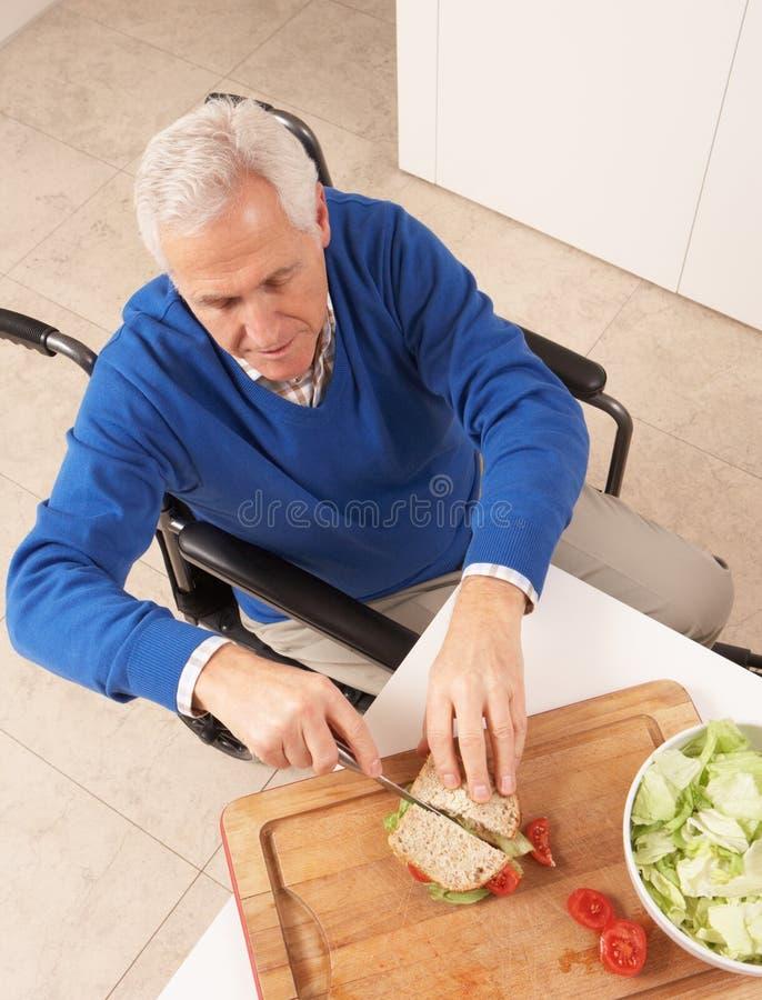 Homme aîné handicapé effectuant le sandwich photographie stock