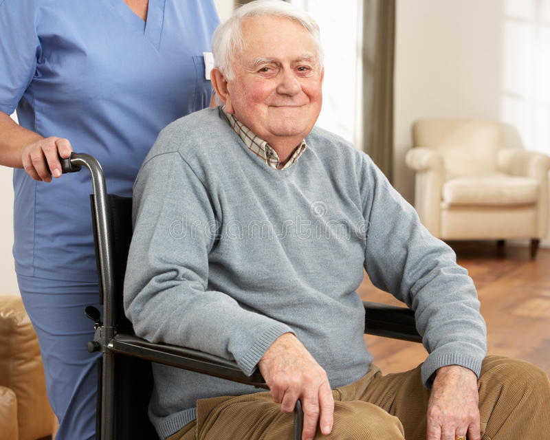 Homme aîné handicapé s'asseyant dans le fauteuil roulant photo libre de droits