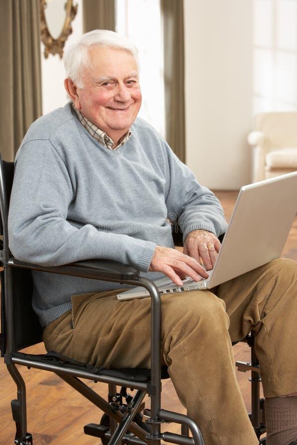 Homme aîné handicapé s'asseyant dans le fauteuil roulant images libres de droits
