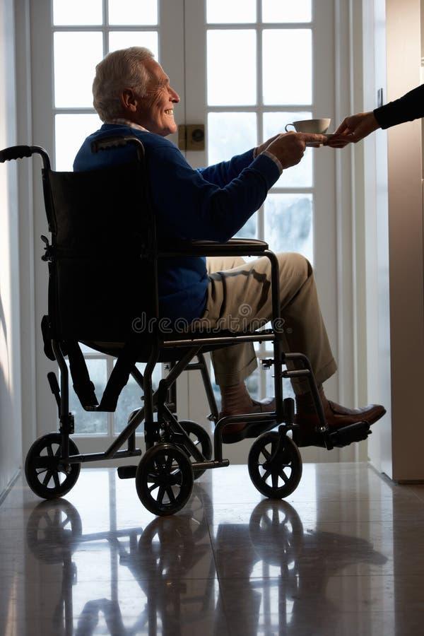 Homme aîné handicapé s'asseyant dans le fauteuil roulant photos stock