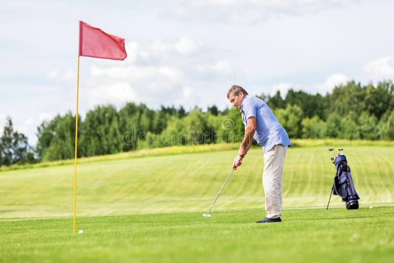 Homme aîné jouant au golf photo libre de droits