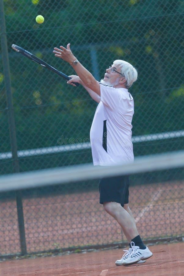 Homme aîné jouant au tennis image stock