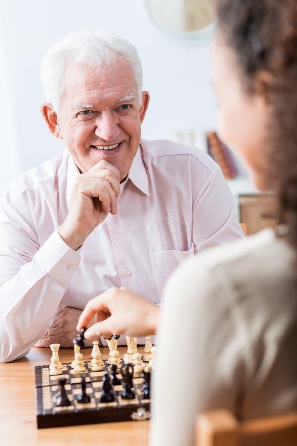 Homme aîné jouant aux échecs photo libre de droits